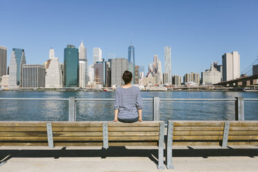 USA, New York City, back view of young woman looking at skyline - GIOF000147