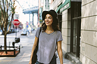 USA, New York City, portrait of smiling young woman wearing black hat - GIOF000156