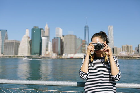 USA, New York City, young woman standing in front of skyline taking a photo with camera - GIOF000162