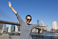 USA, New York City, portrait of happy young woman balancing with outstretched arms - GIOF000165