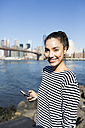 USA, New York City, portrait of smiling young woman with smartphone - GIOF000168