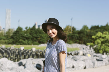 USA, New York City, portrait of smiling young woman wearing black hat - GIOF000171