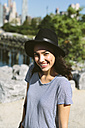 USA, New York City, portrait of smiling young woman wearing black hat - GIOF000174