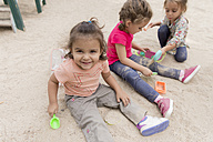 Three little girls playing in the sandbox of a playground - ERLF000041
