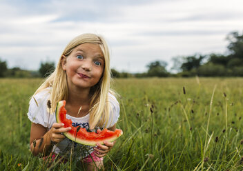 Girl with slice of watermelon standing on a meadow making a face - MGOF000800