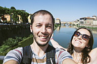 Italy, Florence, happy couple with Ponte Vecchio in the background - GEMF000438