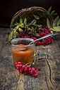 Wickerbasket, rowanberries and glass of rowanberry jam on dark wood - LVF003934