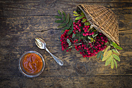 Wickerbasket, rowanberries and glass of rowanberry jam on dark wood - LVF003940