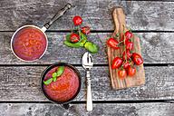 Saucepan and bowl of homemade tomato soup on wood - SARF002156