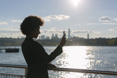 USA, New York City,  businesswoman taking a selfie with smartphone at backlight - GIOF000183