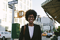 USA, New York City, portrait of smiling businesswoman wearing glasses - GIOF000198