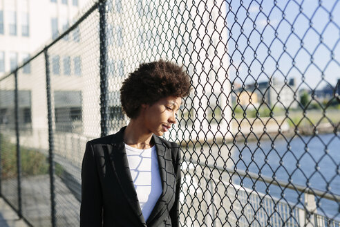 USA, New York City, pensive businesswoman looking through mesh wire fence - GIOF000201