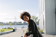 USA, New York City, portrait of smiling businesswoman leaning on railing - GIOF000207