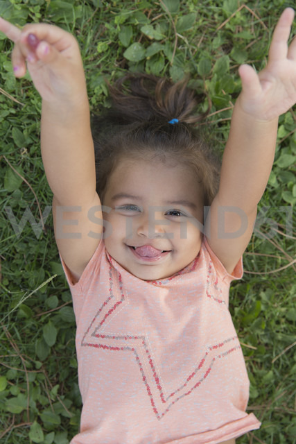 Portrait of smiling little girl lying on a meadow sticking out tongue - ERLF000051