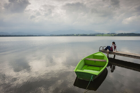 Woman sitting on pier, Hopfensee lake, green rowing boat - WGF000731