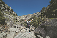 Spain, ultra trail runner looking at the landscape with hands raised, celebrating victory - RAEF000523