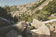Spain, Galicia, A Capela, Ultra trail runner drinking at the canyon of Eume river - RAEF000526