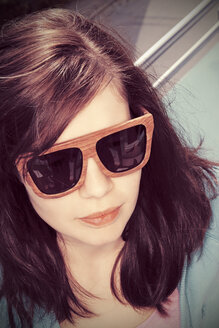 Young woman wearing wooden sunglasses - HOHF001357