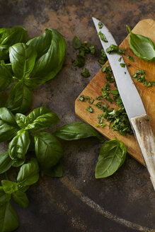 Whole and chopped basil leaves and kitchen knife on wooden board - KSWF001584