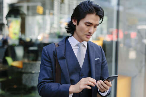 USA, New York City, businessman looking at cell phone in Manhattan - GIOF000212