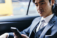 Smiling businessman on back seat of car using cell phone - GIOF000215