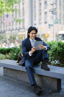 USA, New York City, Manhattan, smiling businessman looking at digital tablet - GIOF000224