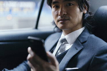 Portrait of businessman on back seat of car with cell phone - GIOF000227