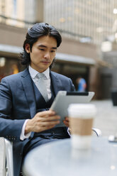 USA, New York City, businessman at outdoor cafe looking at digital tablet - GIOF000230