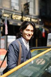 USA, New York City, smiling businessman entering a taxi - GIOF000233