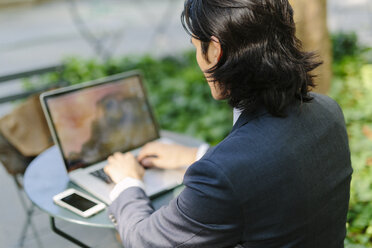USA, New York City, Manhattan, businessman working with a laptop in Bryant Park - GIOF000236