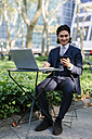 USA, New York City, Manhattan, smiling businessman with laptop and cell phone in Bryant Park - GIOF000242
