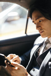 Businessman on back seat of car using cell phone - GIOF000245