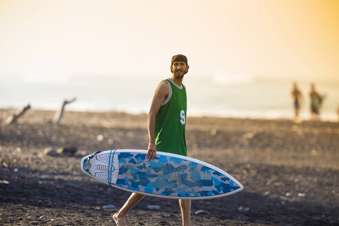 Indonesia, Bali, surfer walking on the beach - KNTF000107