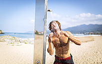 Spain, Asturias, Colunga, young man on the beach taking a shower - MGOF000823