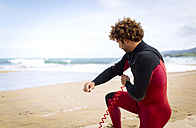 Spain, Asturias, Colunga, surfer preparing on the beach - MGOF000835