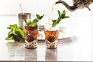 Pouring black tea into traditional North African tea glass with fresh mint leaves - SBDF002287