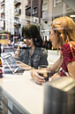Two happy young women in a bar with drinks and digital tablet - JASF000134