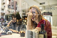Two happy young women in a bar with drinks and digital tablet - JASF000137