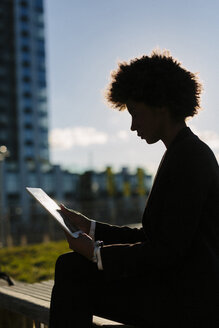 USA, New York City, silhouette of businesswoman looking at digital tablet - GIOF000252