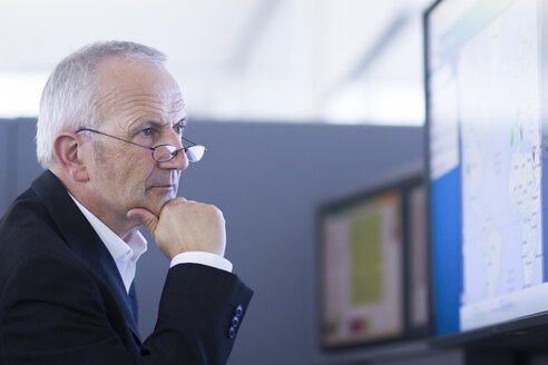 Businessman in office looking at computer screen - SGF001903
