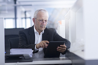Businessman in open space office using digital tablet - SGF001918