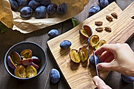 Plums on chopping board, pitting - YFF000462