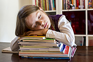 Girl sleeping on stack of school books - SARF002178