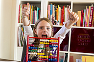 Portrait of cheering girl sitting behind abacus showing thumbs up - SARF002187