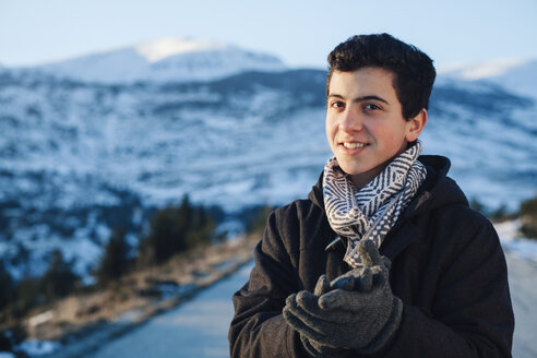 Teenage boy wearing winter clothes, snowy mountains in background - BZF000265