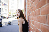Portrait of young woman leaning against brick wall - GIOF000253