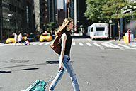 USA, New York City, young woman with rolling suitcase crossing a street - GIOF000262