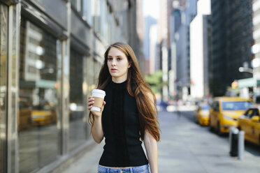 USA, New York City, portrait of young woman with coffee to go - GIOF000265