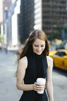 USA, New York City, portrait of smiling young woman with coffee to go - GIOF000268