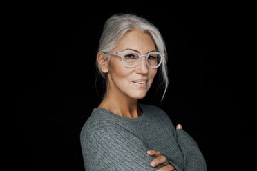 Portrait of smiling woman wearing glasses in front of black background - CHAF001486
